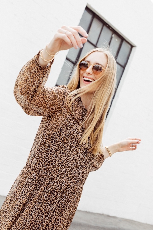 Kimberly Lapides of eatsleepwear wearing a long leopard maxi dress from h&m and golden goose sneakers with ray-ban sunglasses.