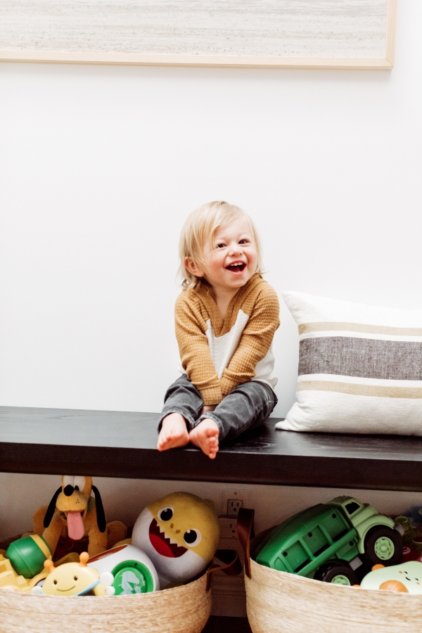 toddler laughing with toys organized under a bench in baskets by Kimberly Lapides of eatsleepwear
