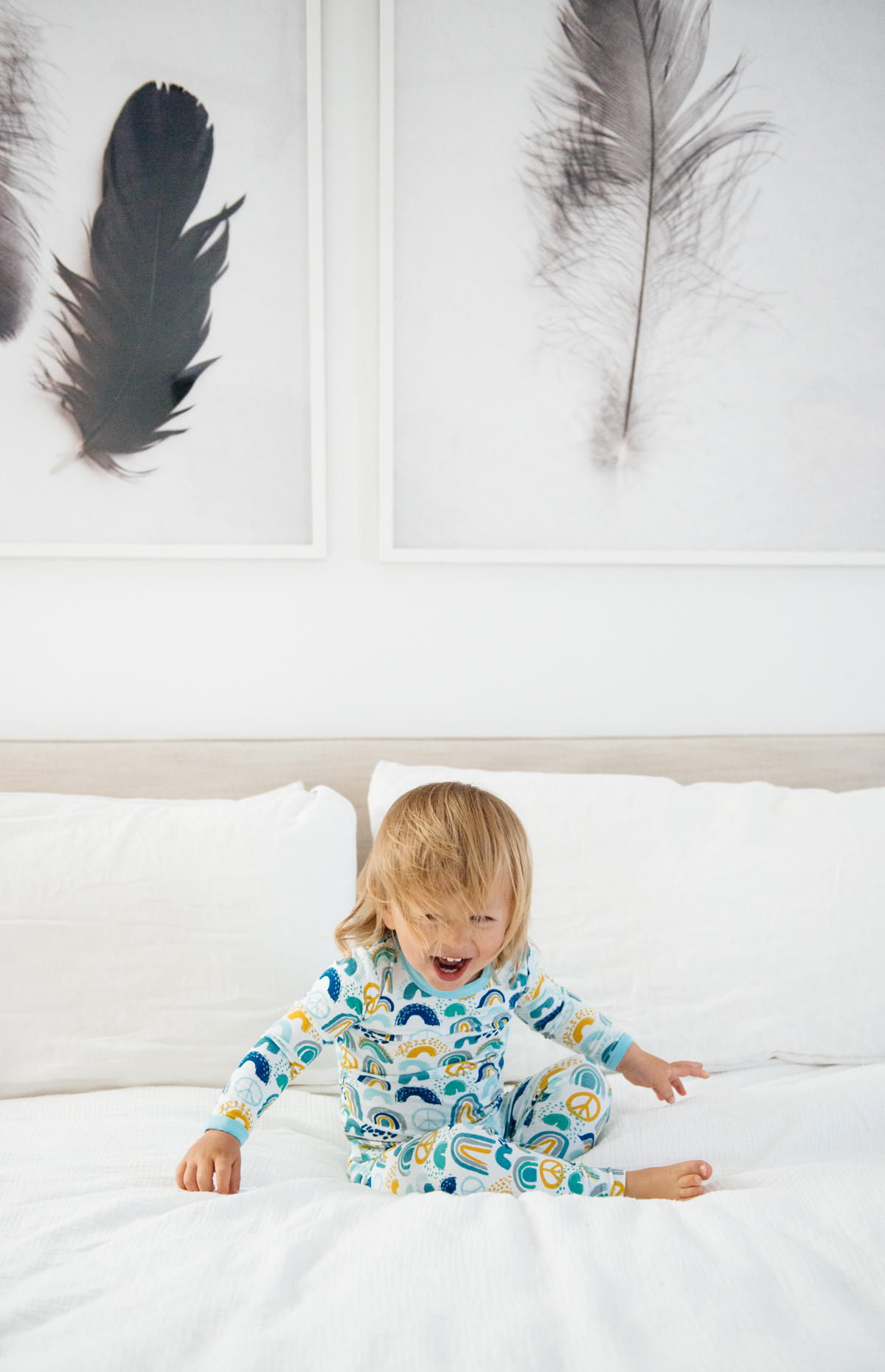 Toddler laughing on bed in Clover Baby & Kids pajamas celebrating Rainbow Baby, IVF, and Infertility