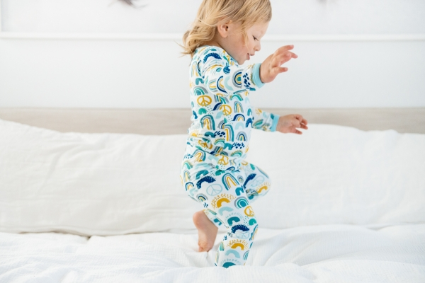 Toddler jumping on bed in Clover Baby & Kids pajamas celebrating Rainbow Baby, IVF, and Infertility