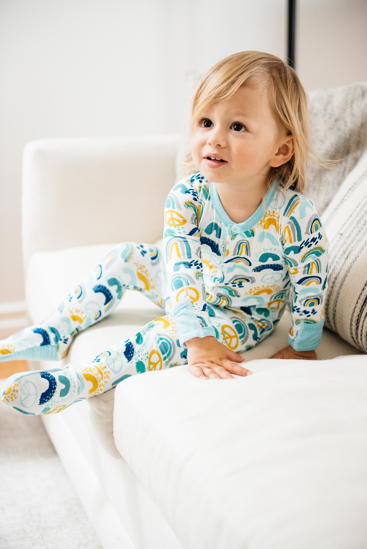 toddler on couch wearing Clover Baby & Kids pajamas celebrating Rainbow Baby, IVF, and Infertility