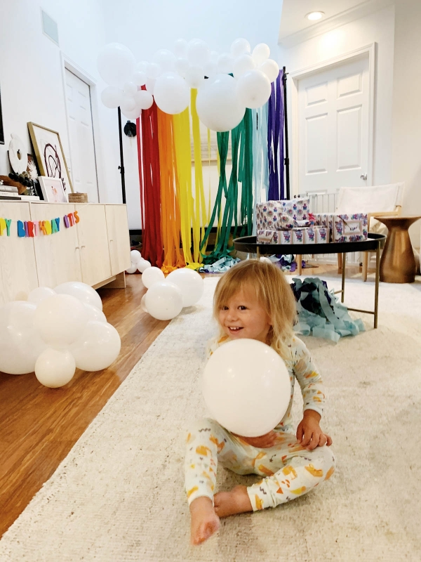 Otis holding balloons and DIY Rainbow and cloud balloon arch with streamer backdrop for Trolls Themed Birthday