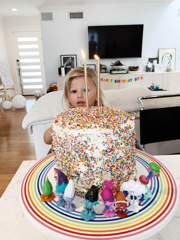 Otis eating DIY rainbow sprinkle cake with Trolls figurines for Trolls theme birthday