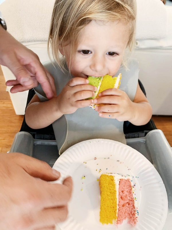 Otis eating rainbow sprinkle cake with Trolls figurines for Trolls theme birthday