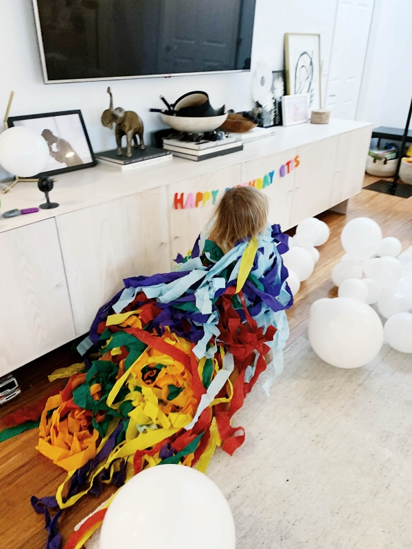 Toddler running with streamers from Trolls theme birthday