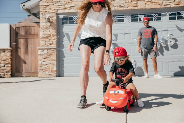 Mom chasing toddler and Ride on Lightning McQueen Car Toy at Disney Pixar Cars themed birthday
