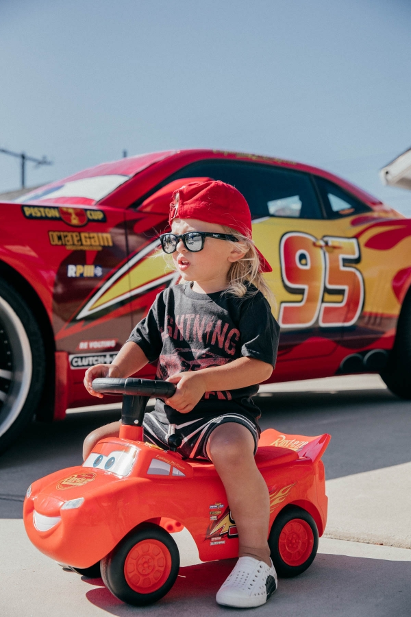 Toddler using Ride On Lightning McQueen Car Toy at Disney Pixar Cars themed birthday