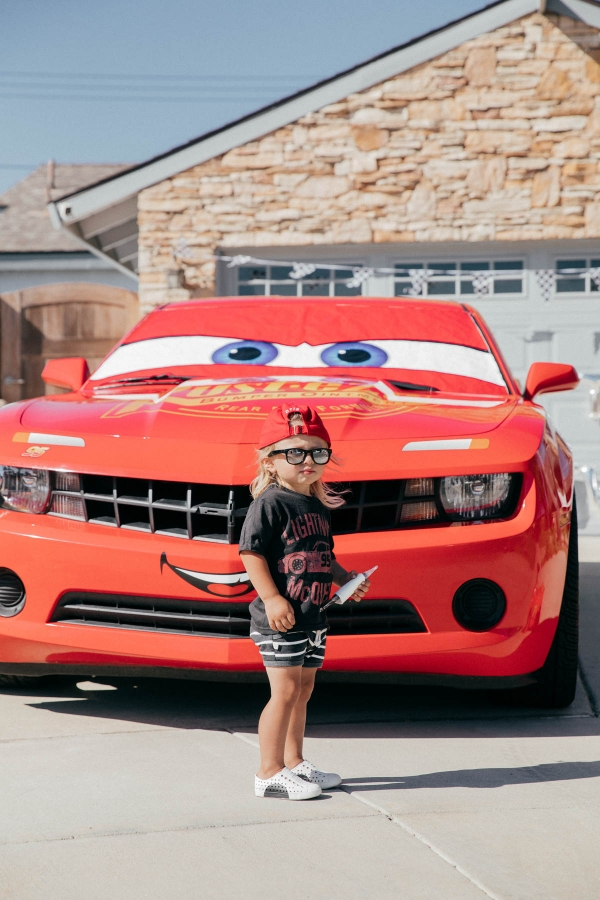 Happy Toddler posing with Lightning McQueen Impersonator Car at Disney Pixar Cars themed birthday