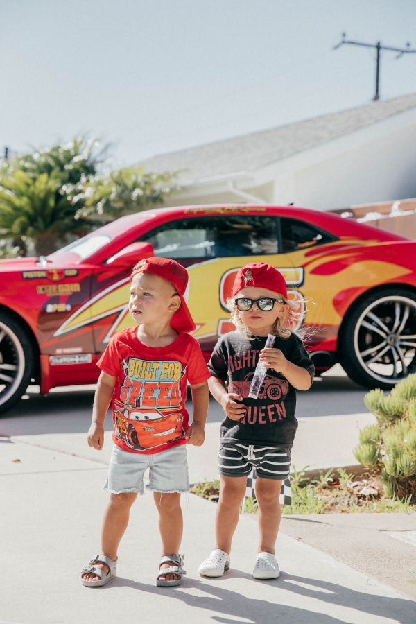 Happy Toddler Fridays posing with Lightning McQueen Impersonator Car at Disney Pixar Cars themed birthday