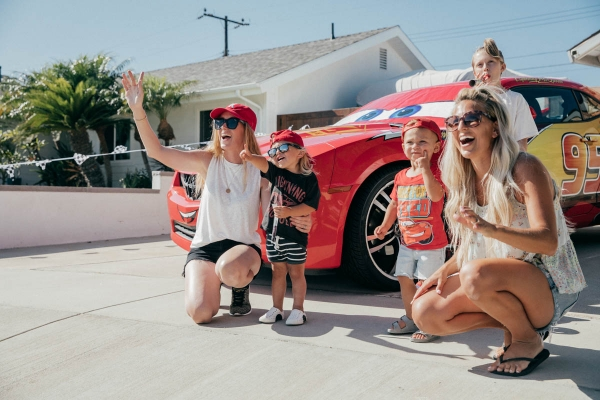 Moms and toddlers posing with Lightning McQueen Impersonator Car at Disney Pixar Cars themed birthday
