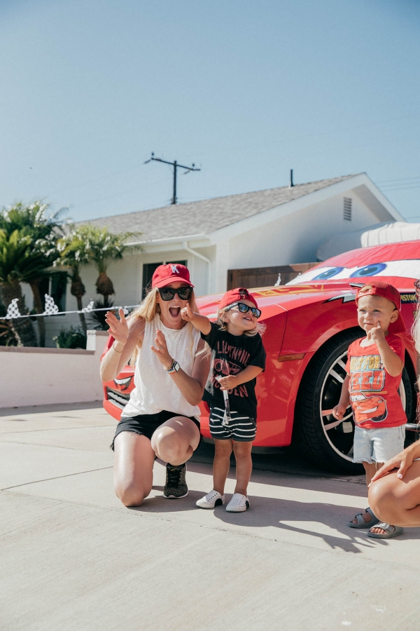 Mom and toddlers posing with Lightning McQueen Impersonator Car at Disney Pixar Cars themed birthday