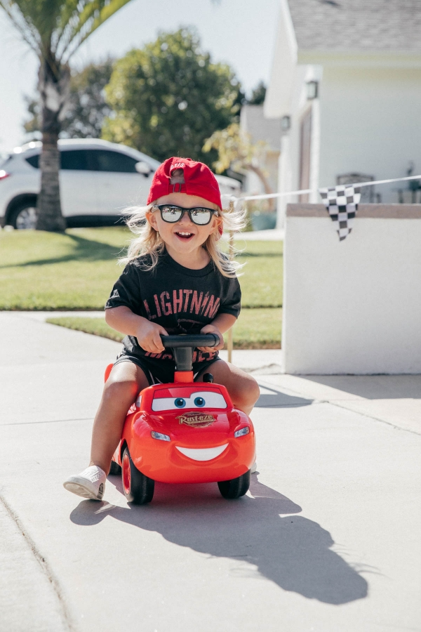 Toddler with ride on Lightning McQueen Car Toy at Disney Pixar Cars themed birthday