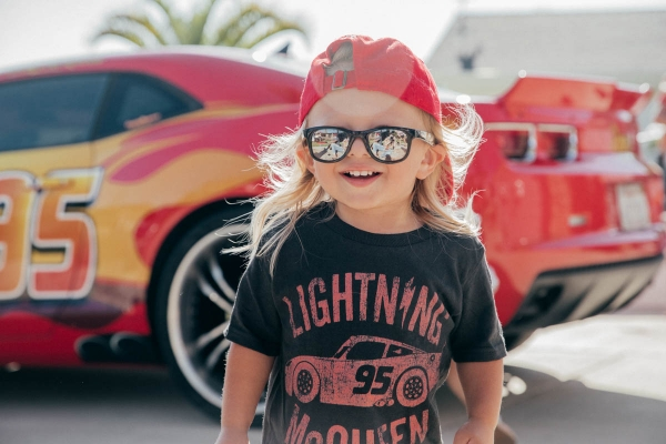 Toddler smiling in front of Lightning McQueen Impersonator at Disney Pixar Cars themed birthday