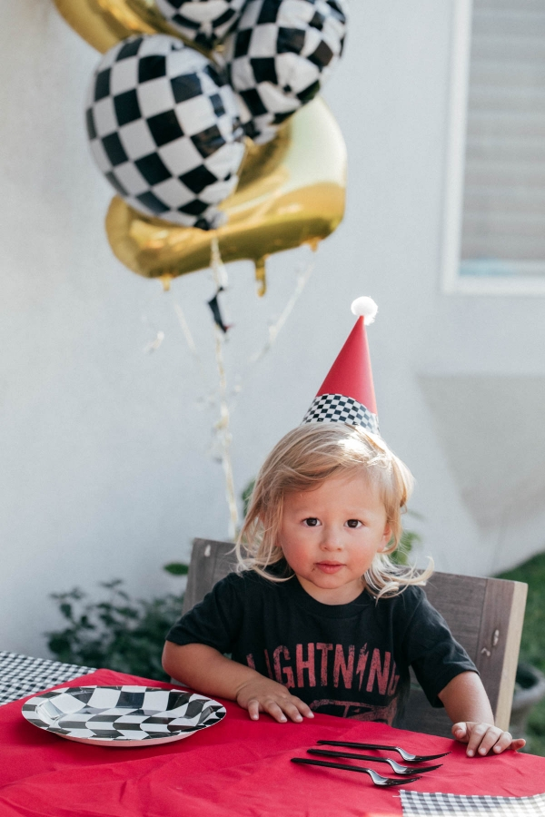 Birthday boy with custom race car party hat and race car theme party decorations at Disney Pixar Cars themed birthday