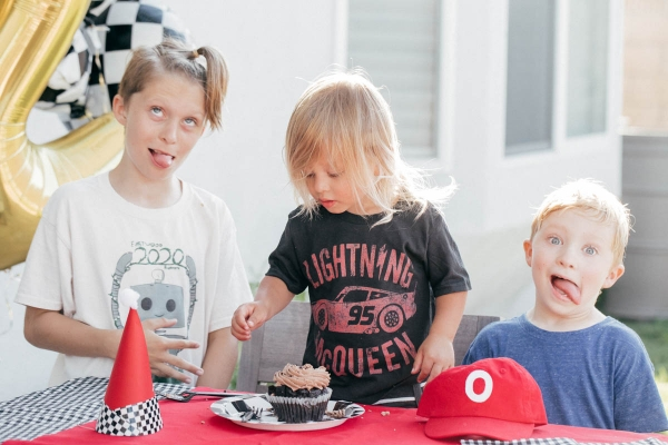 Family Singing Happy Birthday with Cupcake and race car theme decorations at Disney Pixar Cars themed birthday
