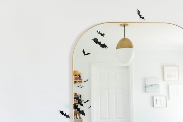 Best Halloween Books for Toddlers styled on wooden shelves with bat wall decals in nursery with modern mirror
