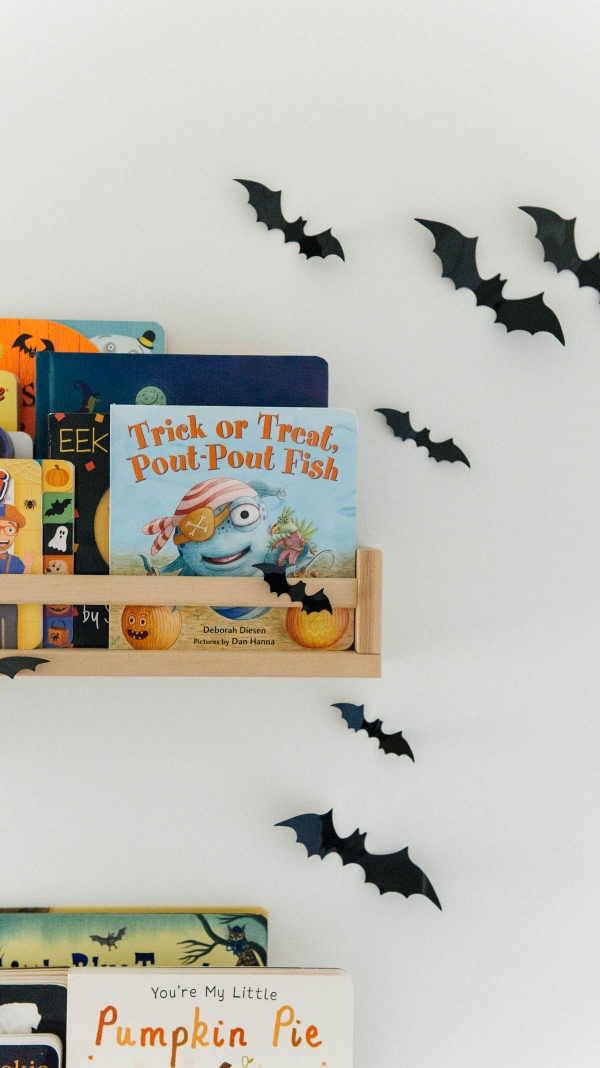 Best Halloween Books for Toddlers styled on wooden shelves with bat wall decals