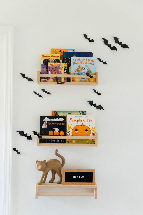 Best Halloween Books for Toddlers styled on wooden shelves with bat wall decals in nursery