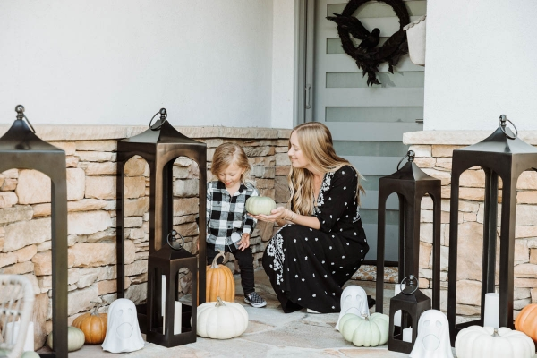 Fall & Halloween Decor For Patio & Yard with Lanterns, faux pumpkins, crow wreath and LED ghosts with toddler holding faux pumpkin