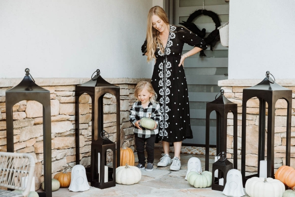 Toddler holding faux pumpkin and Fall & Halloween Decor For Patio & Yard with Lanterns, faux pumpkins, crow wreath and LED ghosts