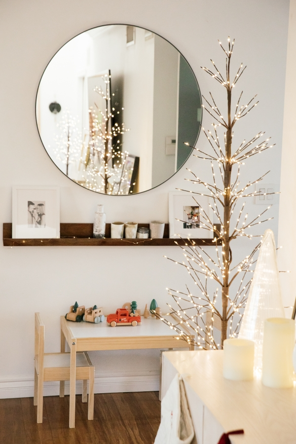 Indoor Holiday decor of twinkle lights tree, twinkle lights, clear glass Christmas tree cloche, kids table and kids Christmas truck toys