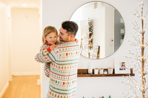 Indoor Holiday decor of twinkle lights tree, twinkle lights, and father and son in Christmas pajamas