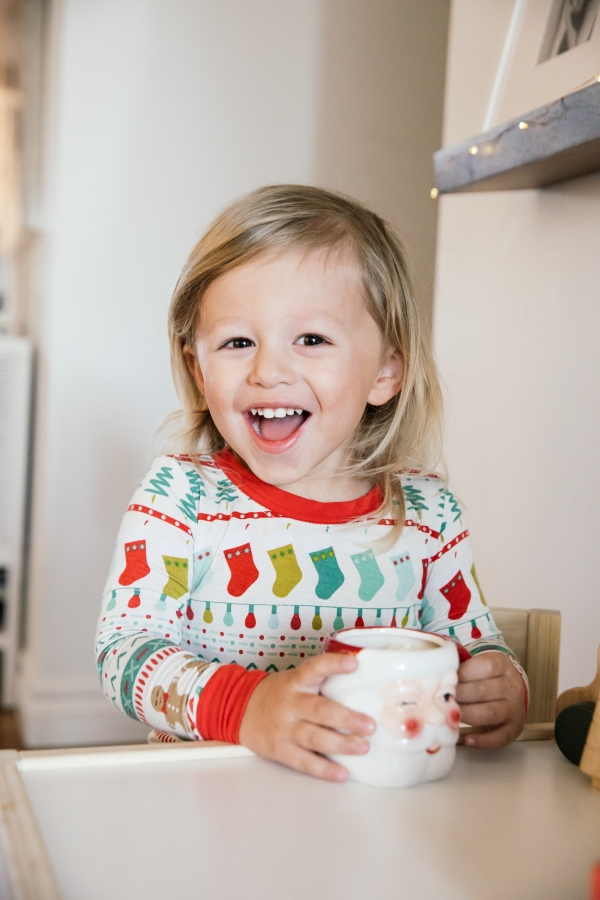 Indoor Holiday decor of toddler sitting at kids table with Santa Clause mugs in Christmas pajamas