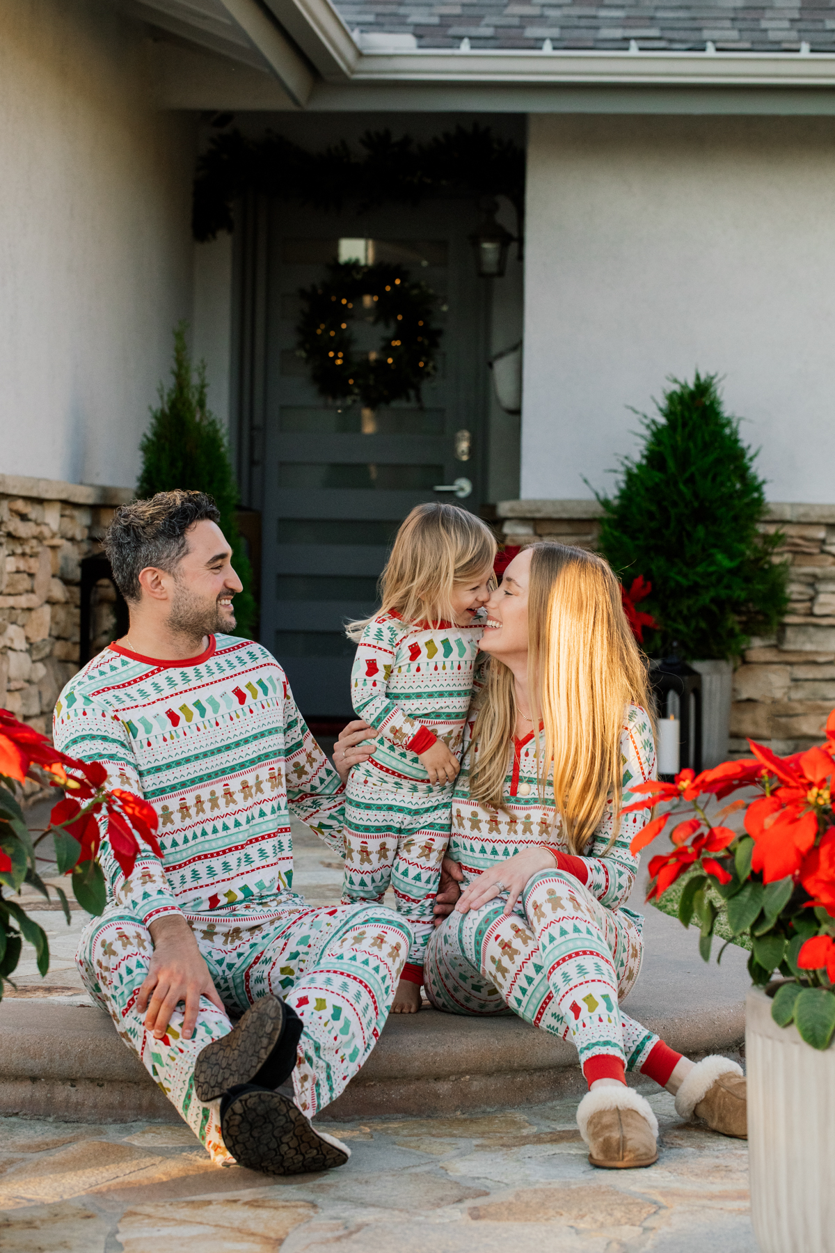 Family sitting outside in holiday Christmas pajamas