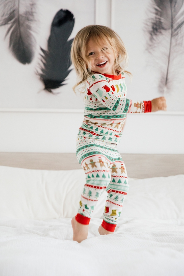 Toddler in Holiday pajamas jumping on the bed