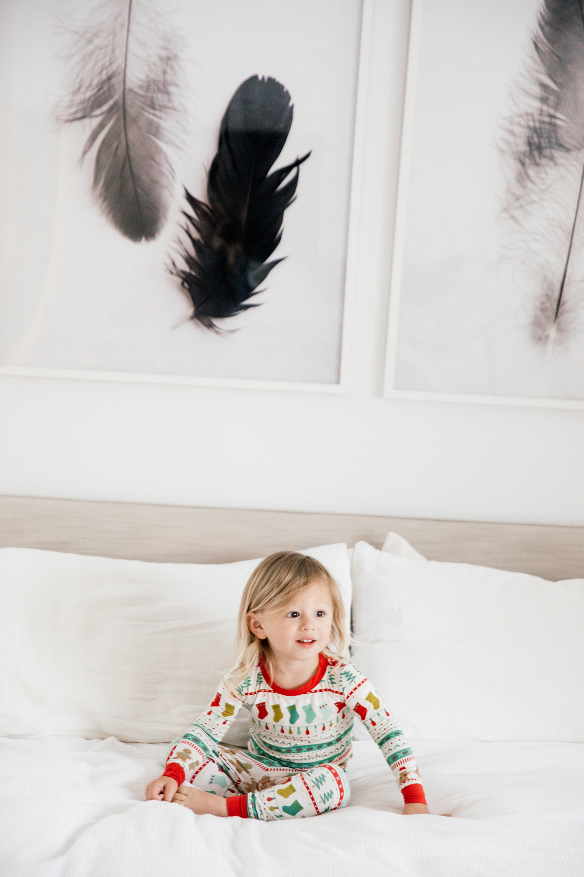 Toddler in Holiday pajamas laughing on the bed