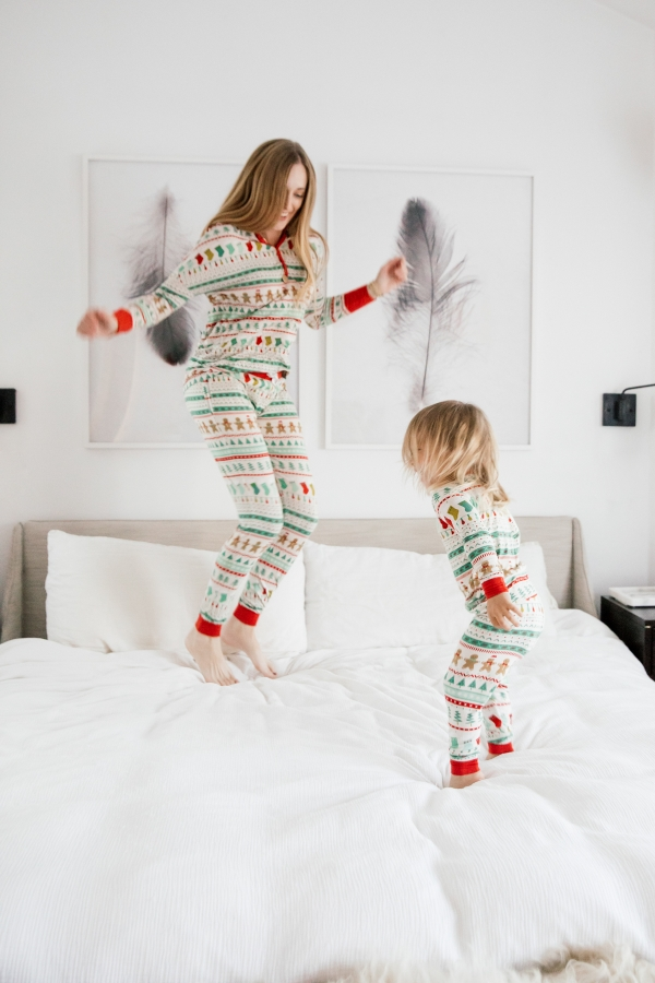 Mother and son in matching Holiday pajamas jumping on the bed