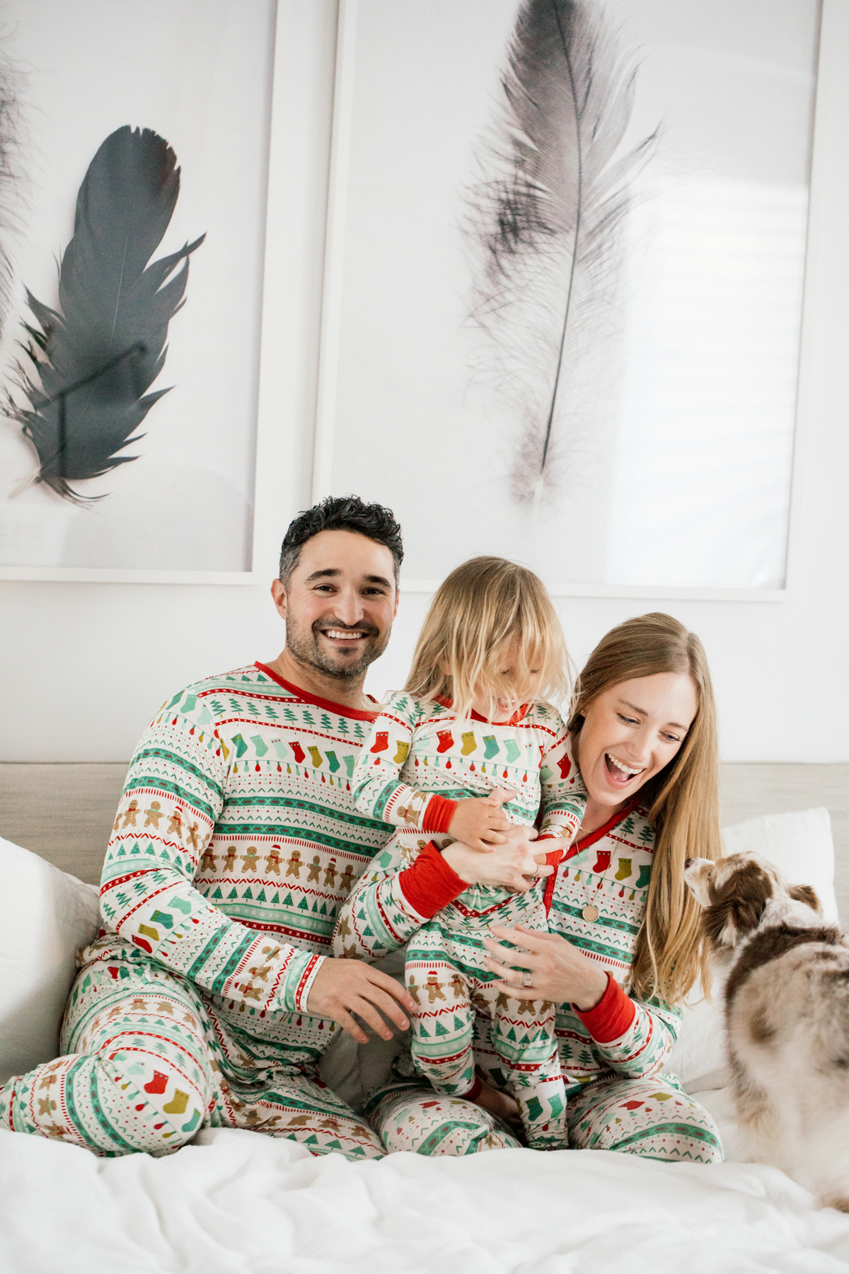 Family in matching Holiday pajamas laughing on the bed