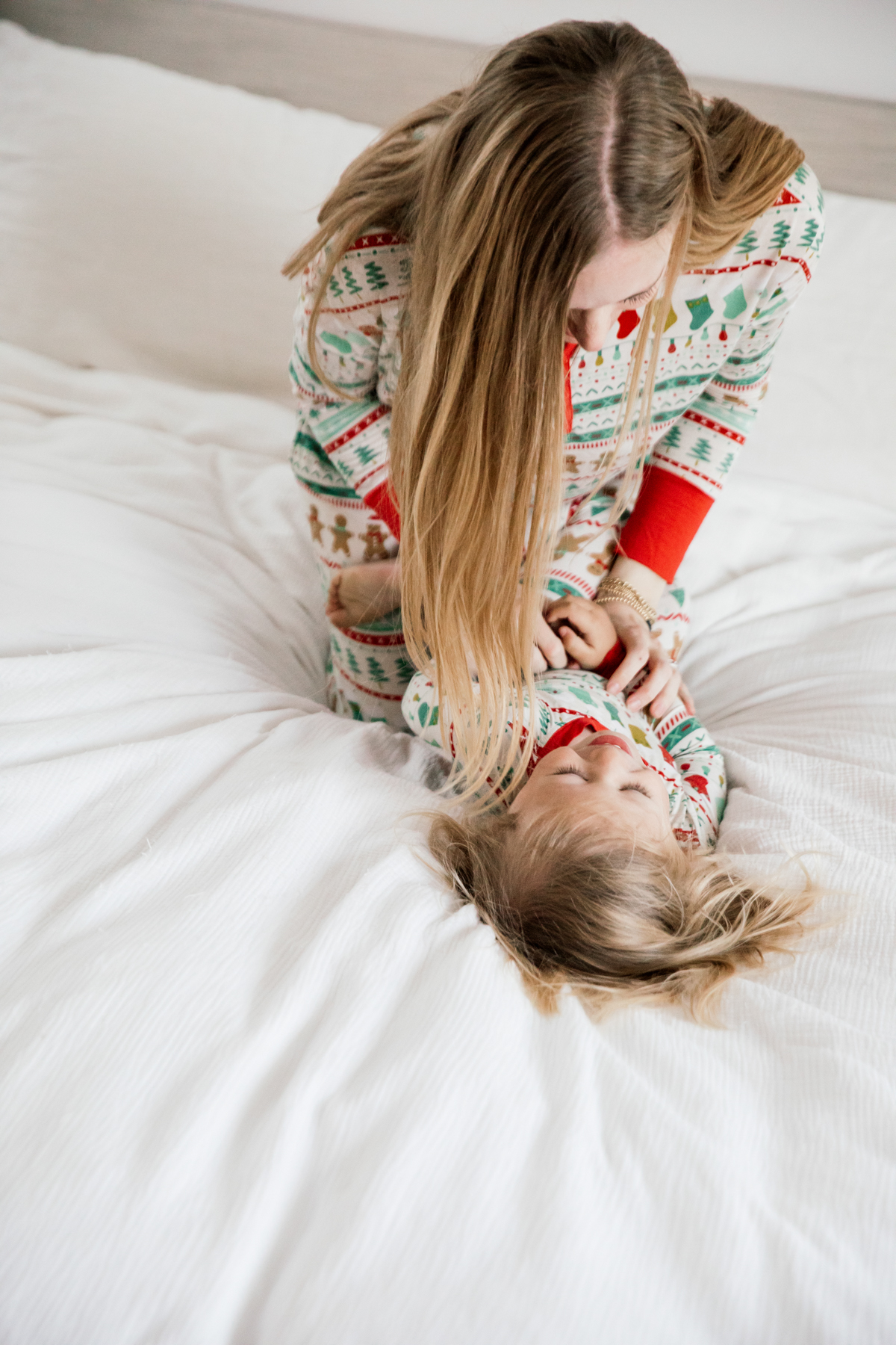 Mother and son in matching Holiday pajamas laughing on the bed